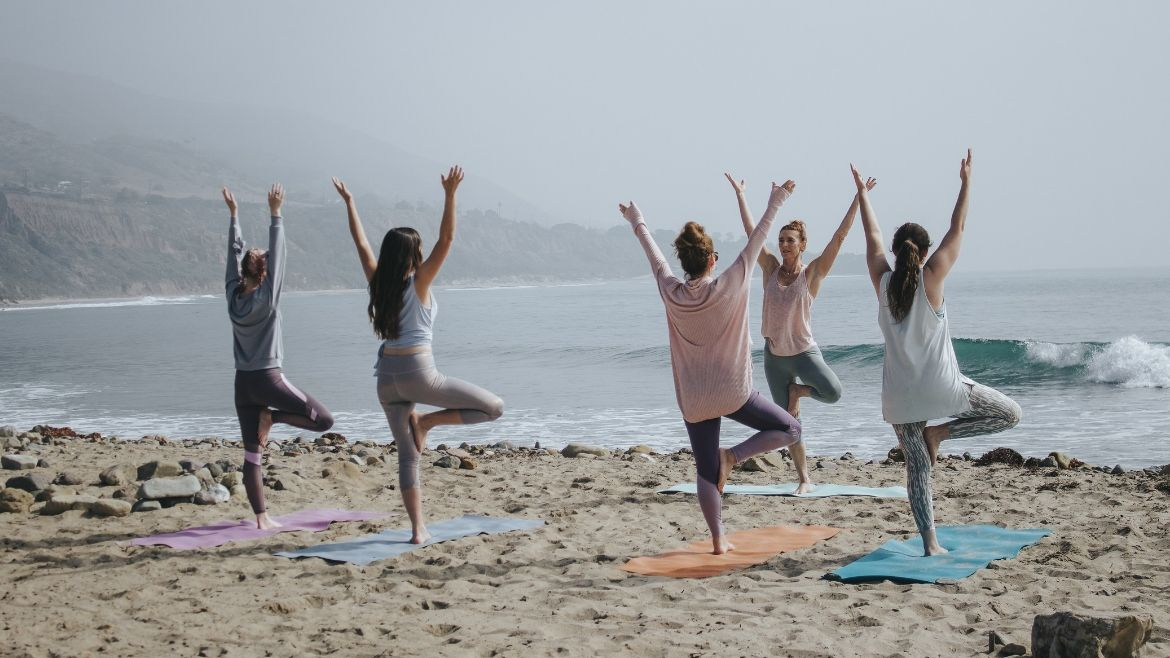A group of women taking a yoga class on the beach