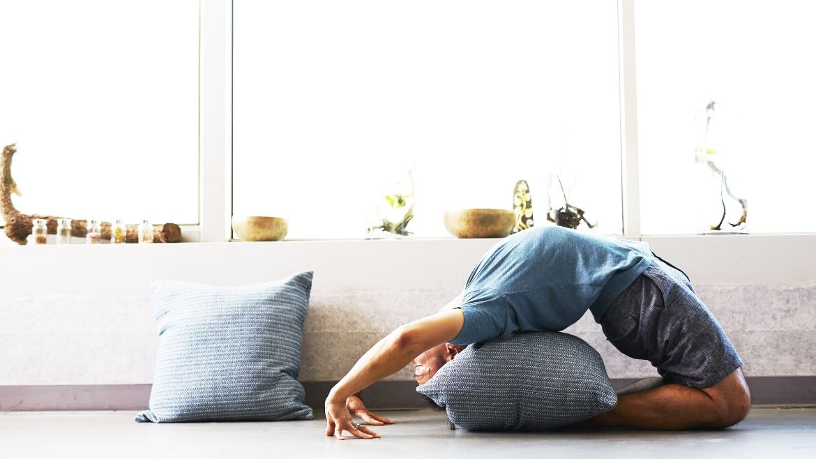 A man doing yoga at home with props