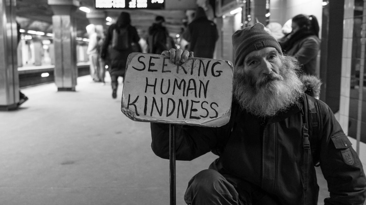 An old man holding a sign saying seeking human kindness