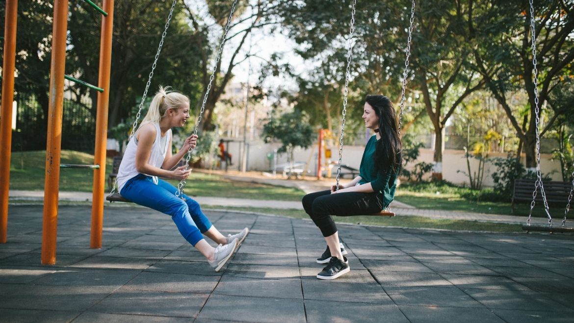 Friends chatting on the swings