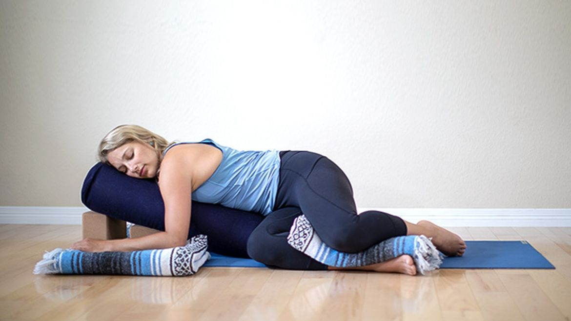 A woman practising restorative yoga
