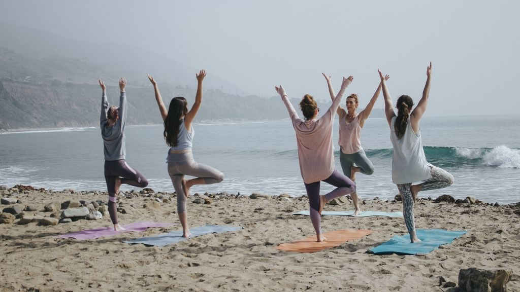 A group of women practising yoga on a beach