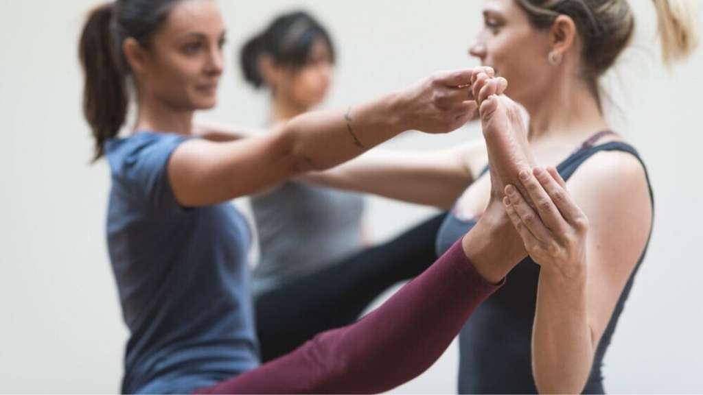 A yoga teacher helping a student