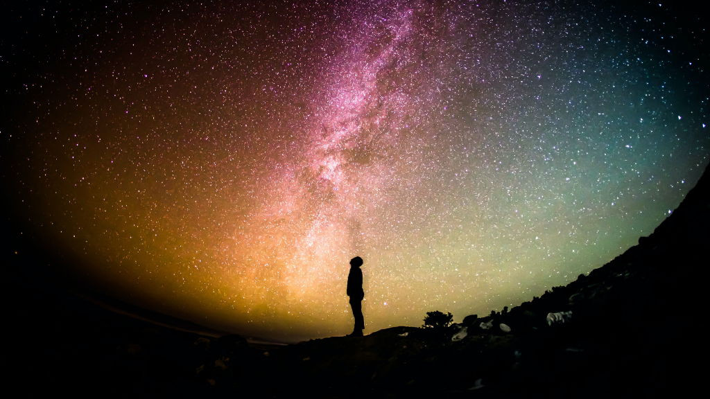Man standing underneath a colourful night sky